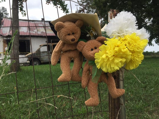 Two teddy bears and some flowers have been tied to