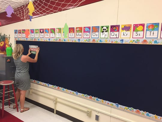 Lauren Trovatten puts the final touches on her ocean-themed classroom. A fishnet with color fish hangs from the ceiling.