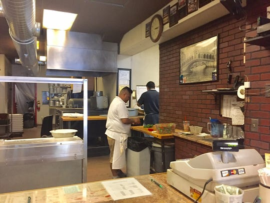 Workers prep for the dinner hour at La Rosa's Pizzeria