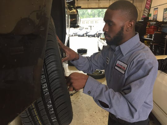 Javon Parker, an auto technician at Paul Campanella's Auto and Tire, puts a hub cap on a tire Wednesday afternoon at the business in Alapocas.