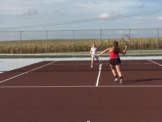 Pleasant girls tennis player Grace Davis, red, returns