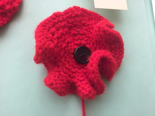 A single red poppy, hand knitted by Sharon Phillips,
