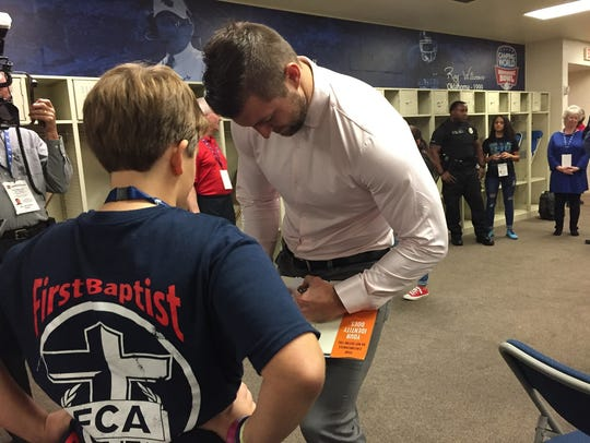Tim Tebow signs a book for FBC fifth grader Sam Conner