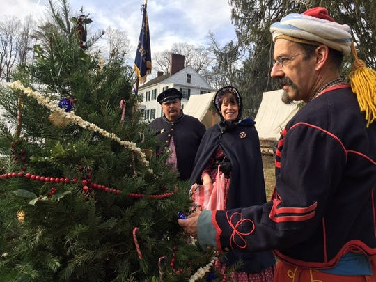 """Decorating the Christmas tree with strings of popcorn and hardtack ornaments at  """"Winter on the Home Front: A Civil War Christmas"""" at Historic Speedwell in Morristown."""