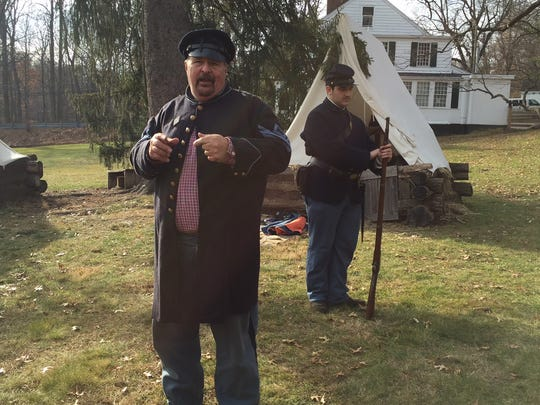 First Sergeant Greg Belcastro of the 7th NJ Regiment explains to the crowd and answer questions about how long it took for a soldier during the Civil War to fire their weapon.