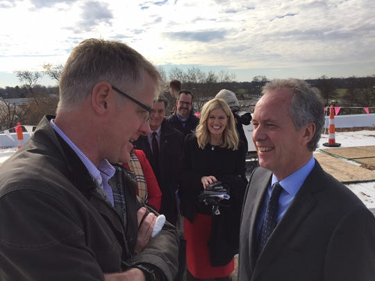 Steve Ricketts with solar-installation company Solar Energy Solutions, at left, talked with Mayor Greg Fischer atop the Oxmoor Center on Monday, amid 2,300 solar panels.
