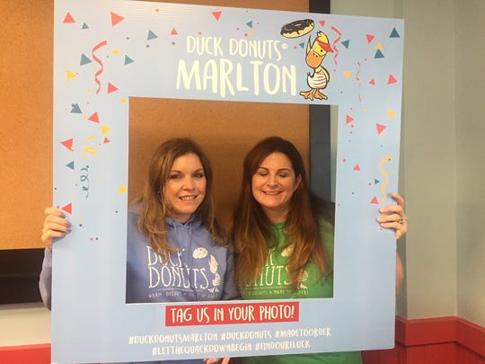 Jennifer Hollander and Nora Branconi smile inside a selfie frame at their new Duck Donuts location at Marlton Crossing.