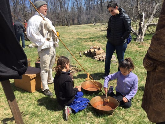 Revolutionary War re-enactors demonstrate camp chores including scrubbing pots at the Grand Encampment at Jockey Hollow on April 21-22, 2018.