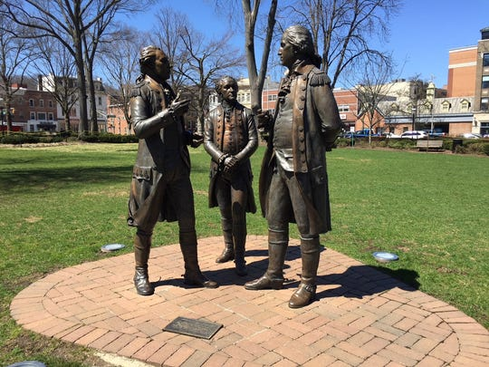 General George Washington, right, and Colonel Alexander Hamilton, center, confer with the Marquis de Lafayette on the Morristown Green.