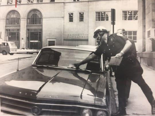 Police Officer Ralph Boryszewski tickets a car outside