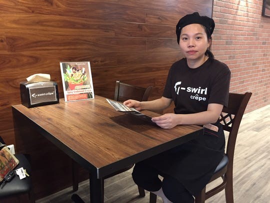 Store manager Mei Lan holds a menu in the new T-swirl