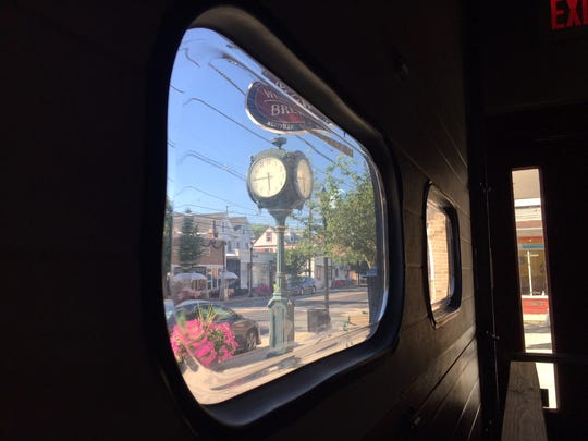 Broadway's clock tower can be seen from a garage door window of Westville Brewery.