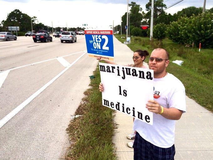 Michelle DeRhodes  and Ryan Kuhn wave to passersby