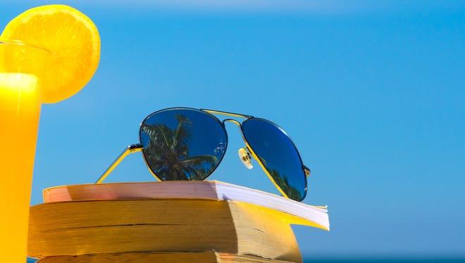 Books and sunglasses on a beach.