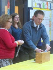 Riverside Elementary School Assistant Principal Kevin Vecellio removes items from a 1991 time capsule Thursday.