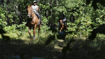 Riding instructor Dawn Harris and student Edward Anderson of Maple Shade ride down the trail after departing Atsion Lake for a ride through the Pine Barrens in Shamong in 2008.