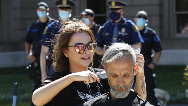 A hair stylist gives a man a free haircut at the State Capitol during a rally as the Michigan State Police watch in Lansing, May 20. More than 60 percent of respondents to a Portland Downtown Development Authority survey stated they would immediately make an appointment with a stylist or massage therapy with social distancing available once the businesses reopen.