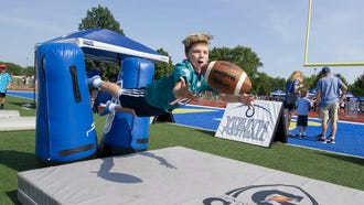 Tommy Brawn, 9, of Westfield, makes a diving catch in the Colts' Youth Football experience at the event. The Indianapolis Colts and the team's mascot, Blue, hosted mascots from around the NFL to as they participated in the third annual Mascot vs. Peewees Football Game at Carmel High School, Thursday, July 12, 2018.
