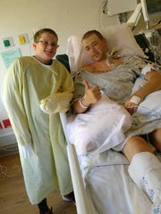 Justin Norenberg gives the thumbs up with his stepson, Ben, after he underwent a double lung transplant.