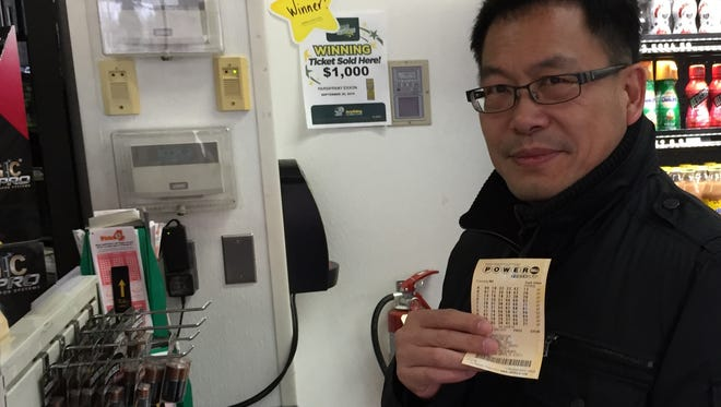 Joe Zhao of Moountain Lakes holds a Powerball ticket he hopes will win him $800 million Saturday at the Exxon station on Route 46 in Parsippany.
