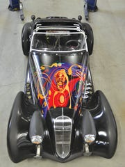 This jet-black two-seater by DiMora Motorcar called a Vicci 6.2 has original artwork on the hood by Chinese painter Won Son Don.