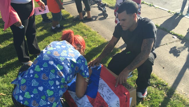 Mourners sign a flag that was hung at the memorial for murder victim Jonathan Padilla outside the David Gantt Community Center on North Street in Rochester.