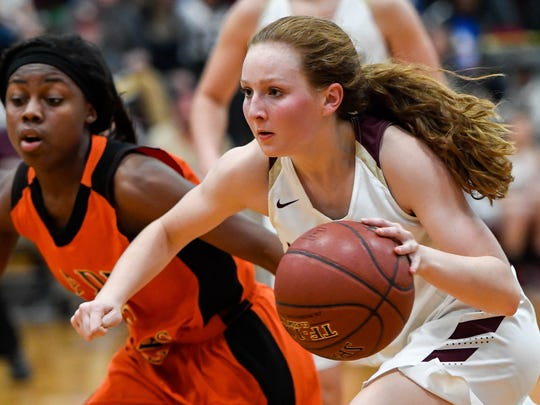 Webster County's Marissa Austin drives against Hopkinsville's Breon Oldham (5) as the Webster County Lady Trojans play the Hopkinsville Lady Tigers in the Second Region semifinals in Dixon Friday, March 2, 2018.