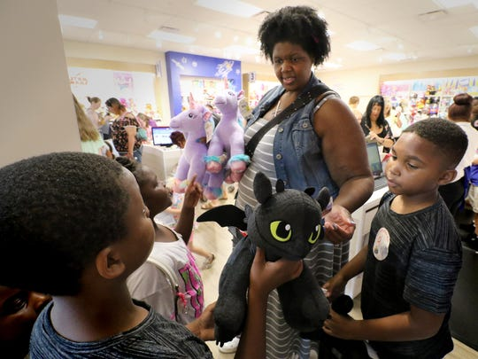 Janelle Olamideolatunji checks the animals created by Melvin (left) and Alexander Wilson during Build-A-Bear's Pay Your Age Day on July 12. Olamideolatunji  volunteered to help the overwhelmed staff at the Mayfair store.
