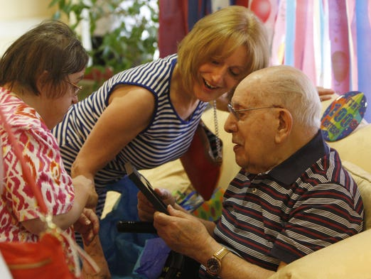 "Anthony Campanella gets a framed birthday gift from his daughter Kathy Campanella, left, as daughter Noreen Roberts looks on at a special 100th Birthday Celebration for him at The Legacy at Cranberry Landing where he lives in Irondequoit on June 8, 2014. ""Tony"", who turns 100 on June 12, is currently the oldest local survivor of the attack on Pearl Harbor, where he was a U.S. Army anti-aircraft gunner."