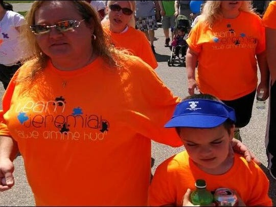 Jeremiah Vaught, now 7, walks with members of his team during last year's Interlock Walk for Autism. His family is getting ready to participate for the fourth time on Saturday raise money to provide children with autism the resources they need.