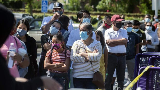 Hundreds of people line up July 3 for free COVID-19 testing in the parking lot of Rancho San Miguel Market in Lodi.