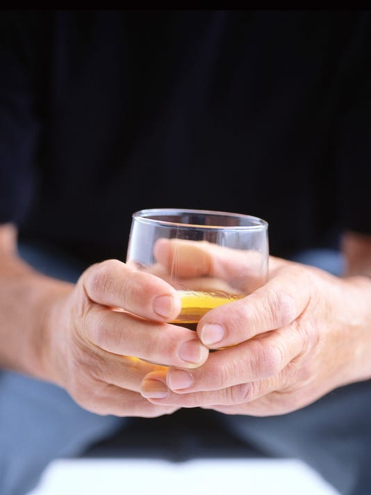 man holding glass of alcohol in his hands
