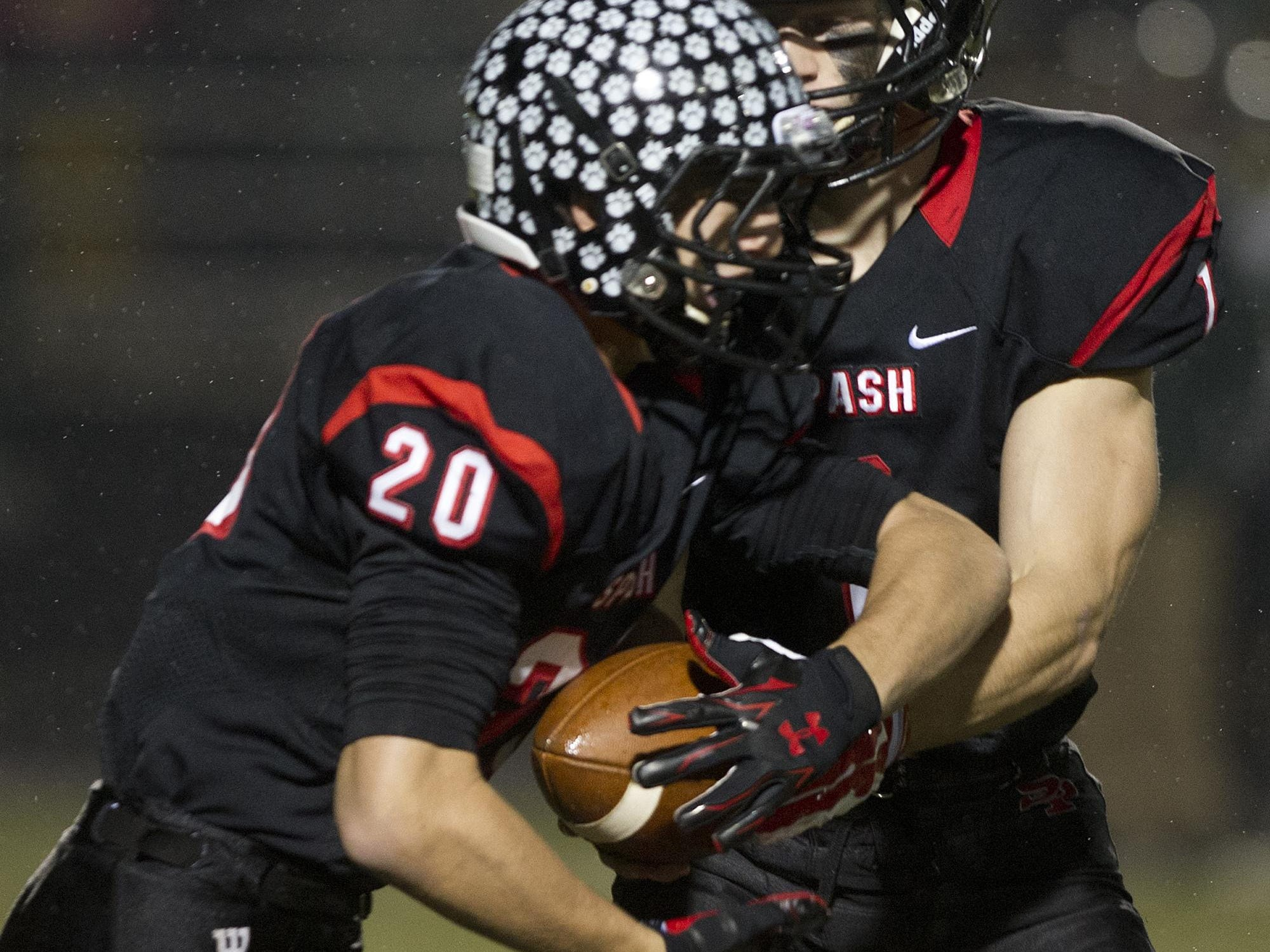 Stevens Point Area Senior High's Victor Kizewski hands off the ball to teammate Gus Turner-Zick during a WIAA Division 1 playoff game Friday against D.C. Everest at Goerke Field in Stevens Point.