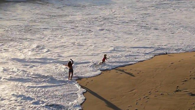 Children play in the surf near Mugu Rock.
