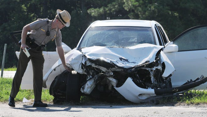 Maryland State Trooper C. Gore, an accident reconstruction trooper, takes measurements at the scene of a serious accident on Route 50 at Sixty Foot Road in Pittsville in this 2011 photo.
