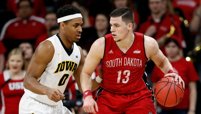 South Dakota guard Matt Mooney (13) drives around Iowa forward Ahmad Wagner, left, during the second half of a first-round game in the NIT college basketball tournament, Wednesday, March 15, 2017, in Iowa City, Iowa. Iowa won 87-75.