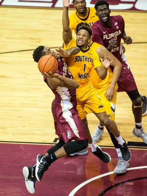 Florida State's Trent Forrest drives to the basket against the Southern Miss' Cortez Edwards.