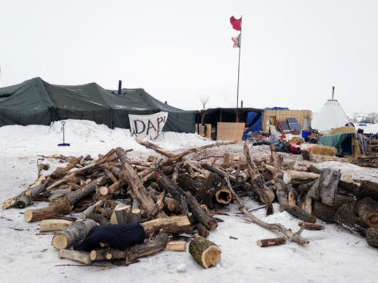 Firewood is stacked up at a protest encampment along