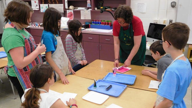 Chaires art teacher Jan Munn demonstrates how to spread this printing ink using a brayer.