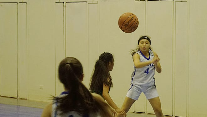 Notre Dame Royals senior Janelle Borja, 4, fires a pass to sophomore Elysia Perez in the Royals' 74-32 home win against the John F. Kennedy Islanders on Friday, Dec. 11.