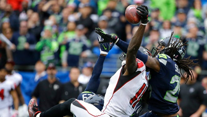Seattle Seahawks cornerback Richard Sherman, right, and Earl Thomas (obscured) break up a pass intended for Atlanta Falcons wide receiver Julio Jones (11) in the second half of an NFL football game, Sunday, Oct. 16, 2016, in Seattle.