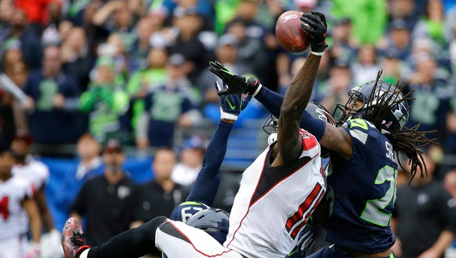 Seahawks cornerback Richard Sherman (right) helps break up a pass intended for Atlanta's Julio Jones in a game earlier this season.