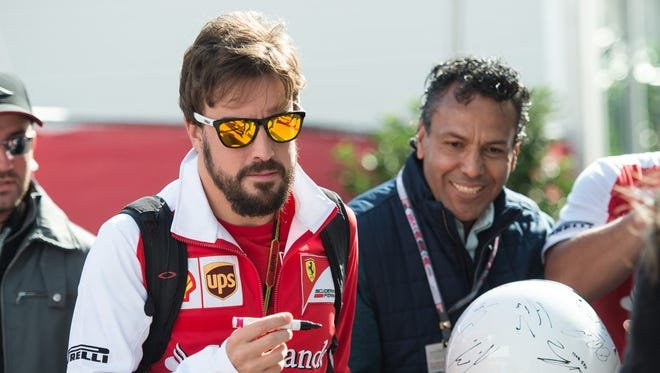 Ferrari driver Fernando Alonso (14) of Spain enters the paddock prior to the 2014 U.S. Grand Prix at Circuit of the Americas.