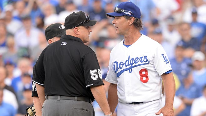 Los Angeles Dodgers manager Don Mattingly speaks with Clive umpire Eric Cooperagainst the St. Louis Cardinals in Game 1 of the 2014 National League Division Series.