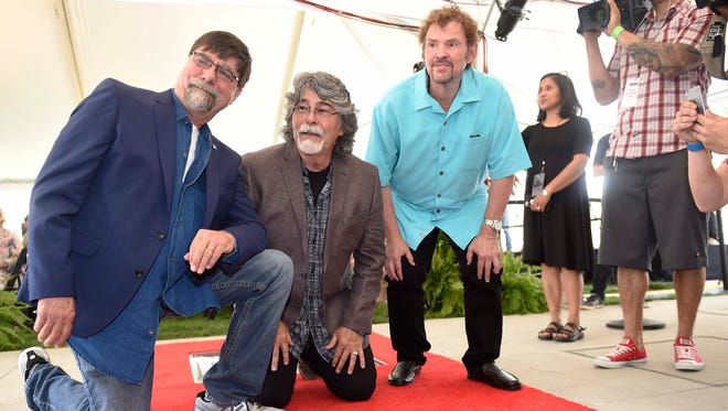 Alabama band members Teddy Gentry, Randy Owen and Jeff Cook pose during the Walk of Fame induction ceremony at Walk of Fame Park on May 26, 2016, in Nashville.