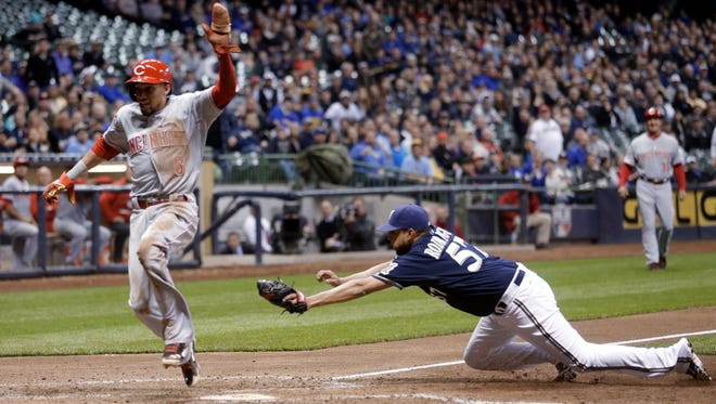 The Reds' Billy Hamilton scores the go-ahead run on a wild pitch past a diving Francisco Rodriguez during the ninth inning Wednesday at Miller Park.
