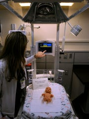"""Kayla Ortiz, a nurse at Hendrick Medical Center's new Neonatal Intensive Care Unit, demonstrates the control panel on a Giraffe Omnibed where a mannequin of a one-pound """"micro-preemie"""" premature baby has been placed."""