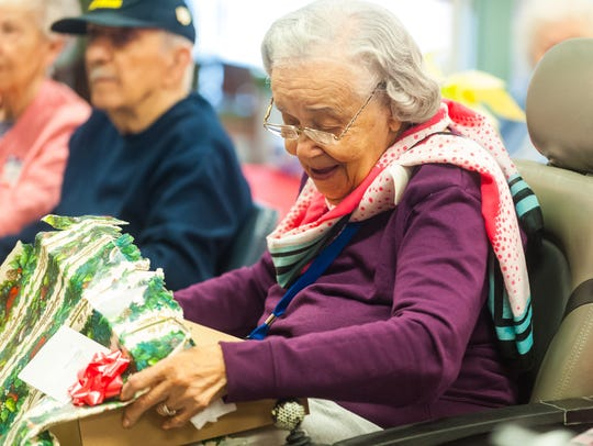 Residents of Veterans Memorial Home up a gift during the Second Wind Dreams Christmas at the Vineland Veterans Memorial Home on Wednesday, December 20.