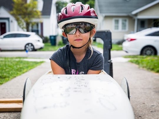 Kaylee Wallace fine tunes her soap box derby racer with her father and grandfather at their Muncie home.  The Wallaces have raced in the soap box derby for four generations.