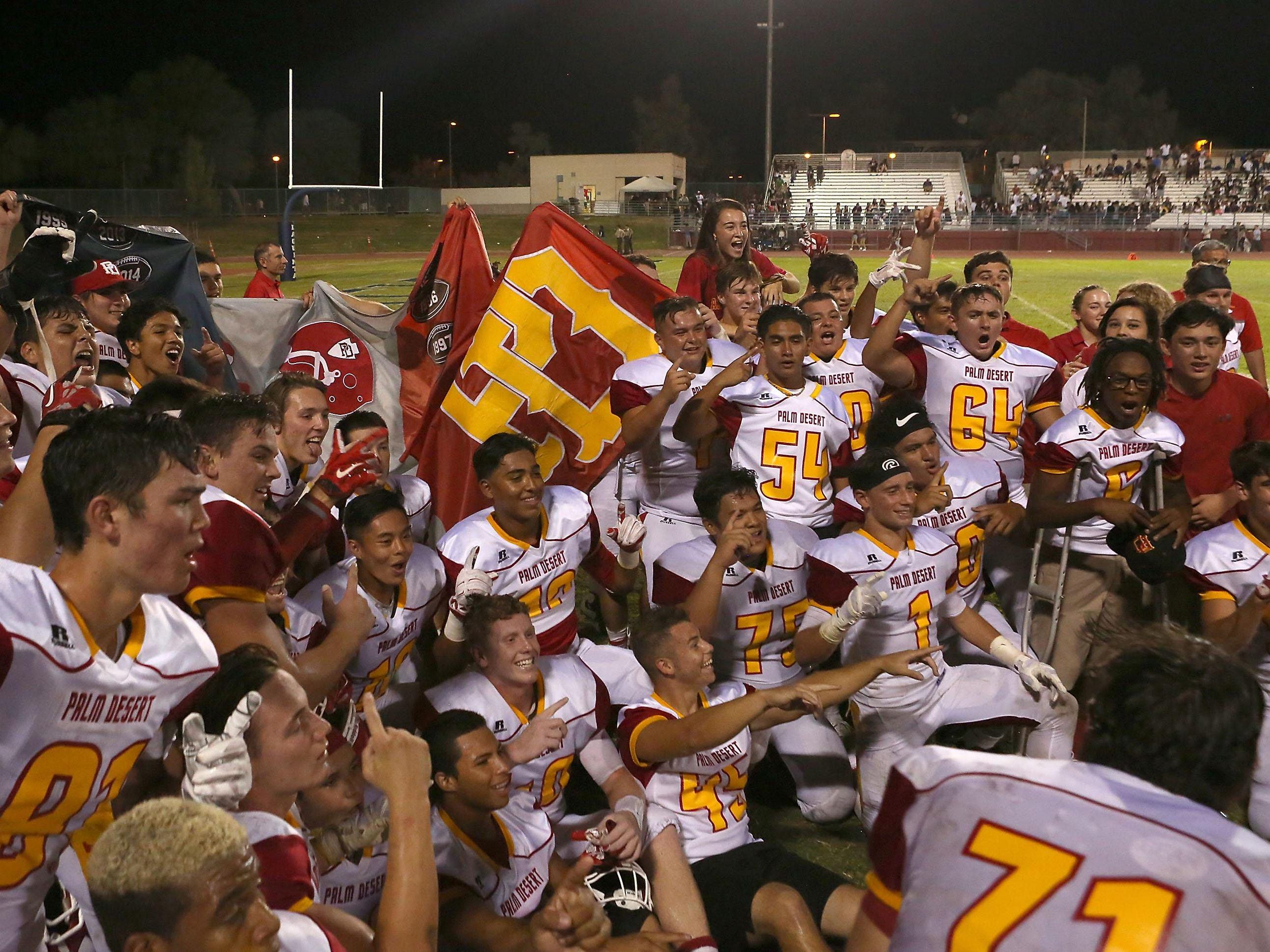 The Palm Desert Aztecs celebrate their victory over La Quinta, Friday, September 25, 2015.